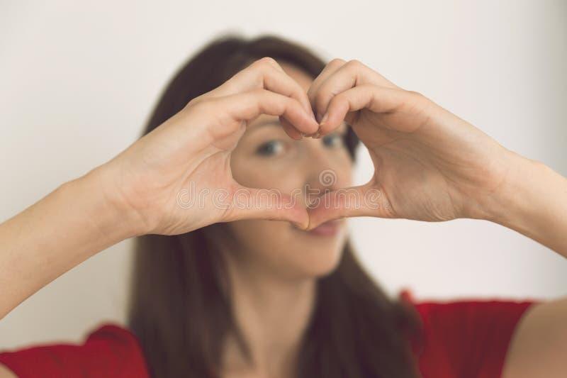 De mooie jonge vrouw in rode kleding toont de hand s van de hartvorm stock afbeelding