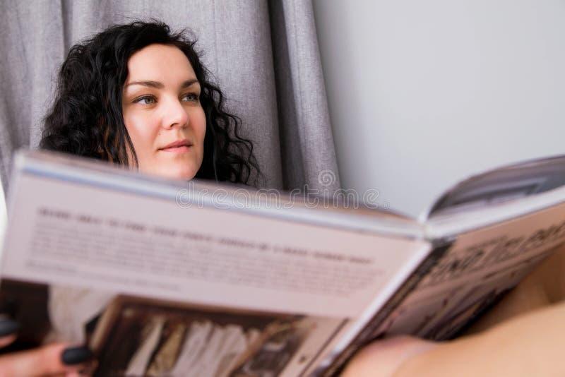 De mooie jonge vrouw rust achter thuis het lezen van een tijdschrift royalty-vrije stock fotografie