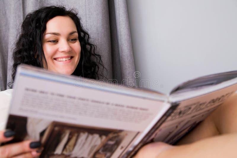 De mooie jonge vrouw rust achter thuis het lezen van een tijdschrift royalty-vrije stock afbeeldingen