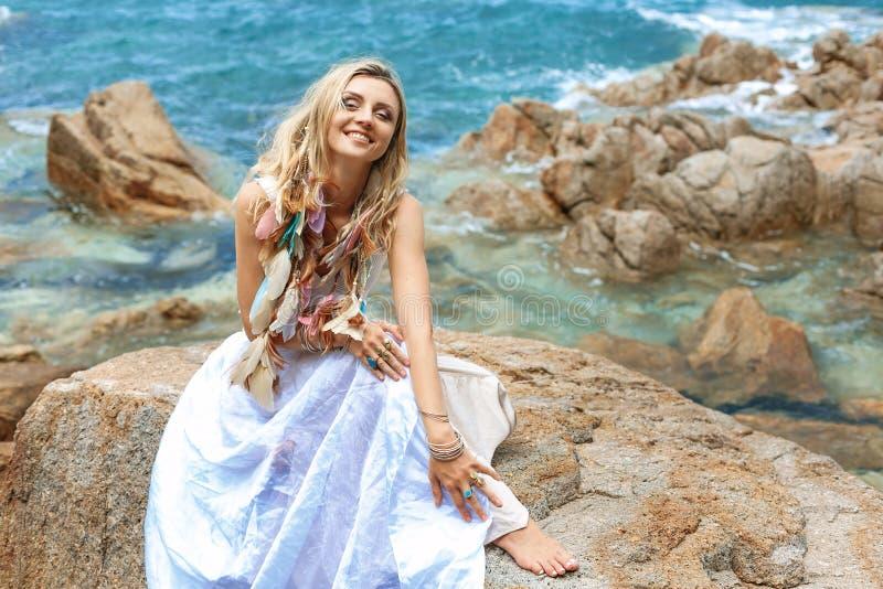 De mooie jonge vrouw van de bohostijl in witte kleding op steenstrand royalty-vrije stock afbeeldingen