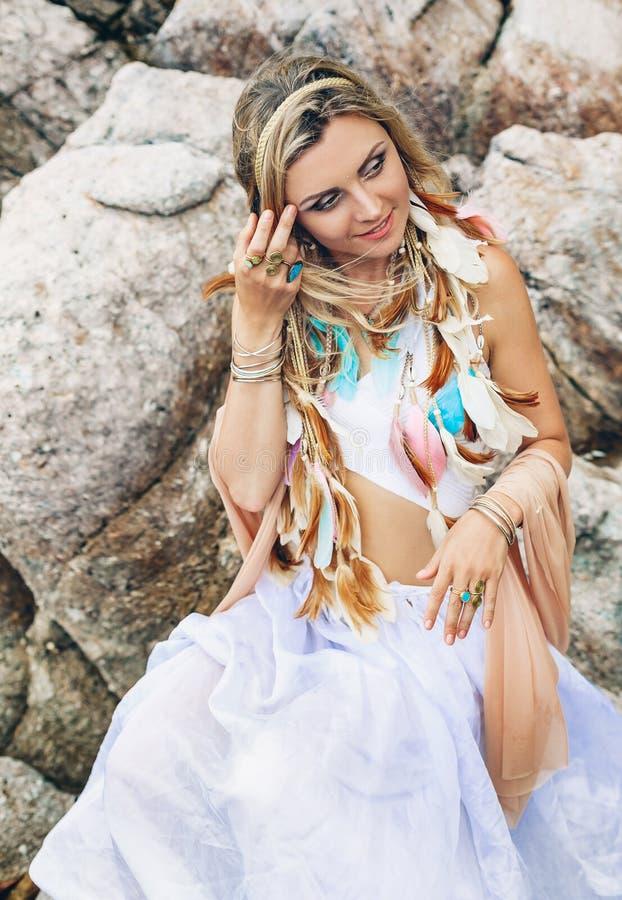 De mooie jonge vrouw van de bohostijl in witte kleding op steenstrand royalty-vrije stock foto's