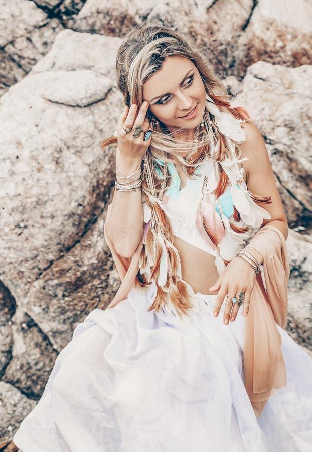 De mooie jonge vrouw van de bohostijl in witte kleding op steenstrand royalty-vrije stock afbeelding