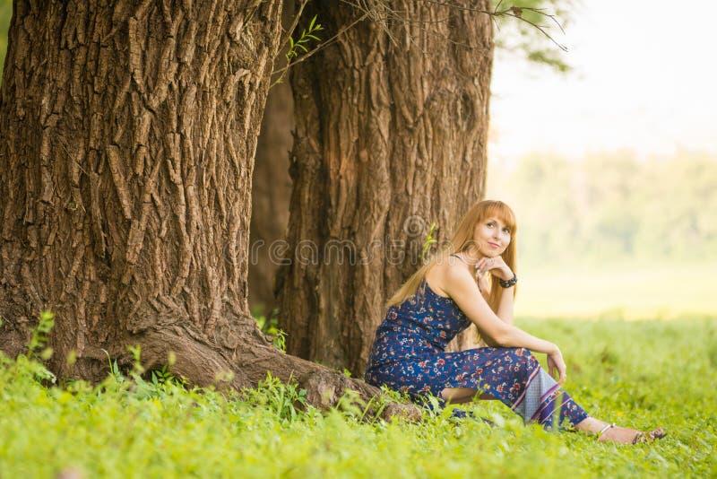 De mooie jonge vrouw zat op wortels van de oude grote boom en keek omhoog dreamily royalty-vrije stock afbeelding