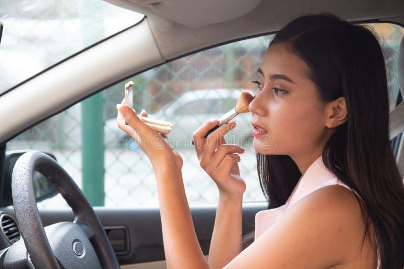 De mooie jonge vrouw zit in auto op bestuurderszitplaats bekijkend achteruitkijkspiegel het controleren, omhoog maakt het borstel stock afbeelding