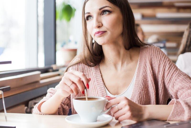 De mooie jonge vrouw zit bij een lijst in een koffie met een kop van koffie en kijkt uit het venster stock afbeelding