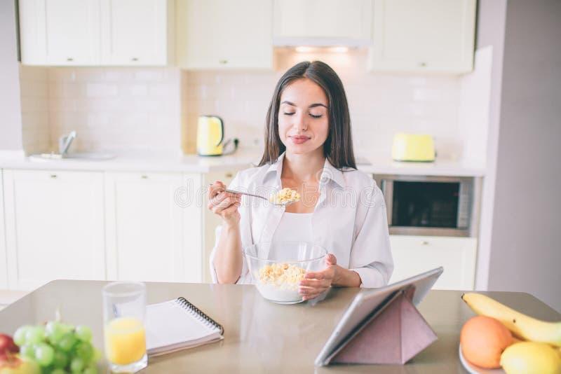 De mooie jonge vrouw zit bij lijst en eet melk met cornflakes Zij houdt lepel met het Het meisje bekijkt lepel stock foto