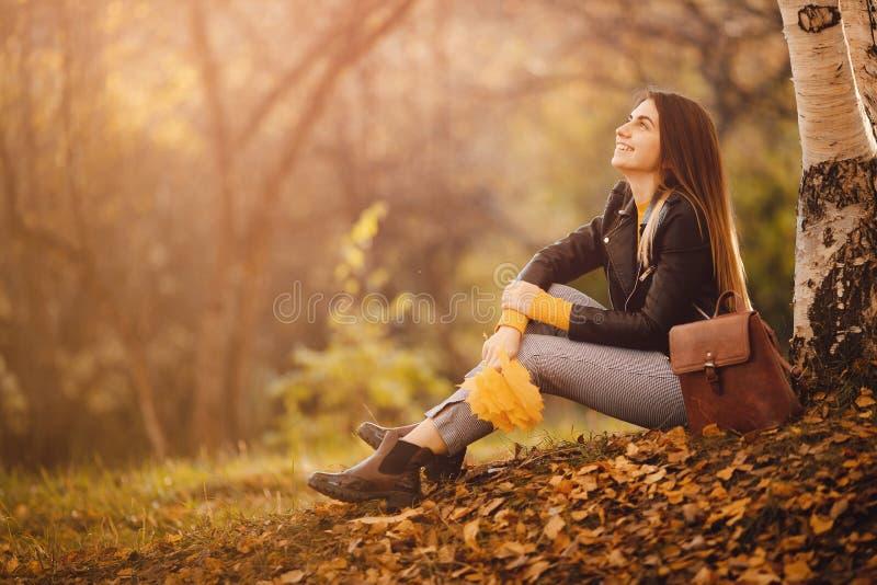 De mooie jonge vrouw zit in de herfstbos in gele blouse met esdoornbladeren en geniet van het leven Het concept van de vrijheid stock foto