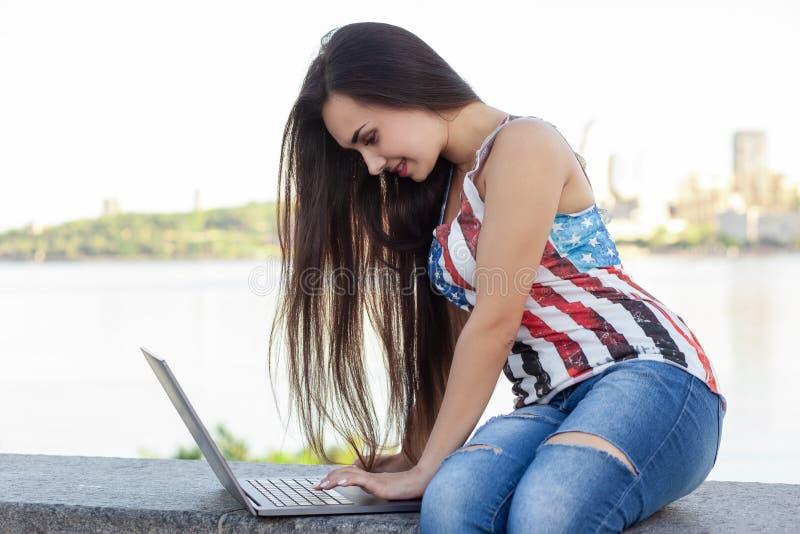 De mooie jonge vrouw zit in het park dichtbij rivier met laptop stock afbeelding