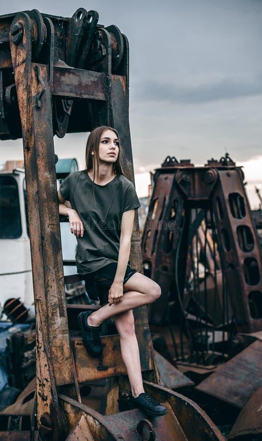 De mooie jonge vrouw zit op een metaal roestig detail, een verlaten fabriek stock afbeeldingen