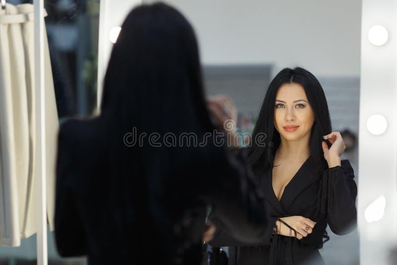 De mooie jonge vrouw zorgt voor een kleding dichtbij een spiegel stock afbeelding