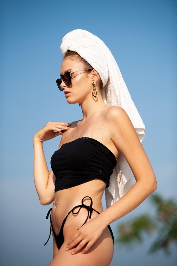 De mooie jonge vrouw zwemt kostuum binnen het stnading op de rand van een hotelpool stock foto's