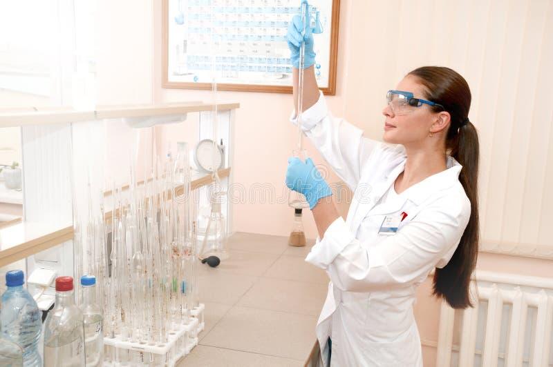De mooie jonge vrouwelijke reageerbuis van de wetenschapperholding en het bekijken het royalty-vrije stock afbeelding