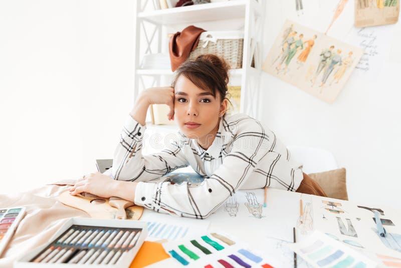 De mooie jonge vrouwelijke zitting van de manierontwerper bij haar het werkbureau royalty-vrije stock afbeeldingen