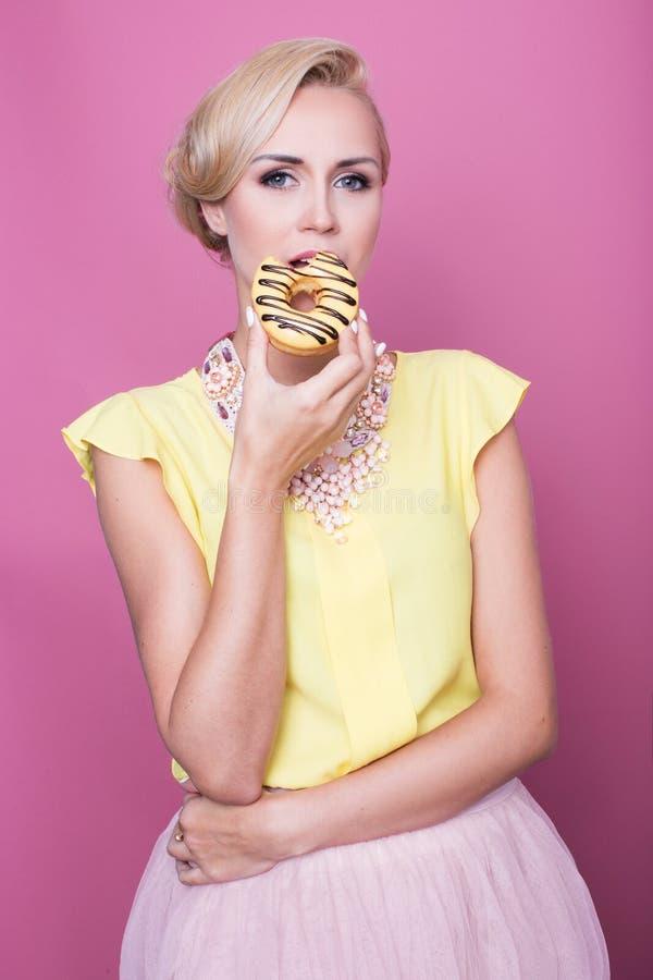 De mooie jonge vrouwen met gele blouse proeven geel dessert Het schot van de manier Zachte kleuren royalty-vrije stock afbeelding