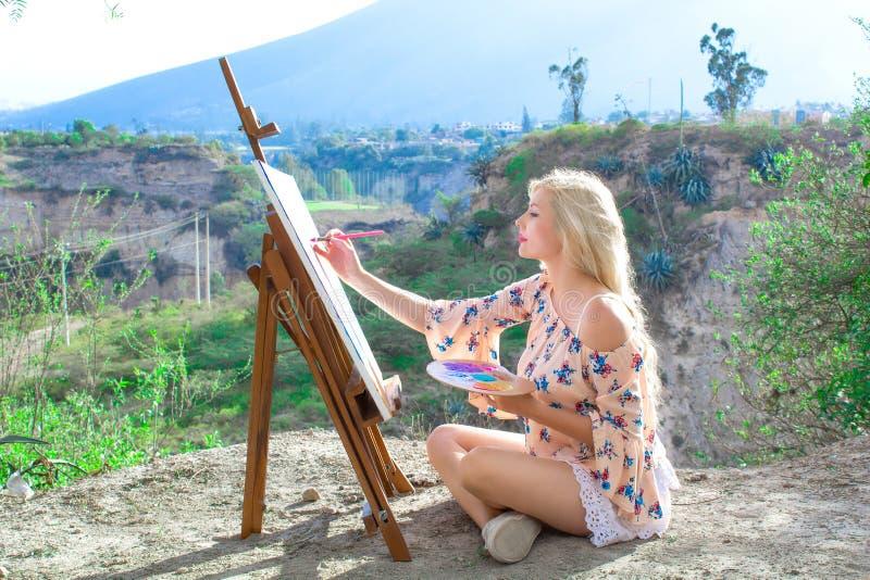 De mooie jonge vrouwenkunstenaar schildert een landschap in aard Het trekken op de schildersezel met kleurrijke verven in openluc stock foto