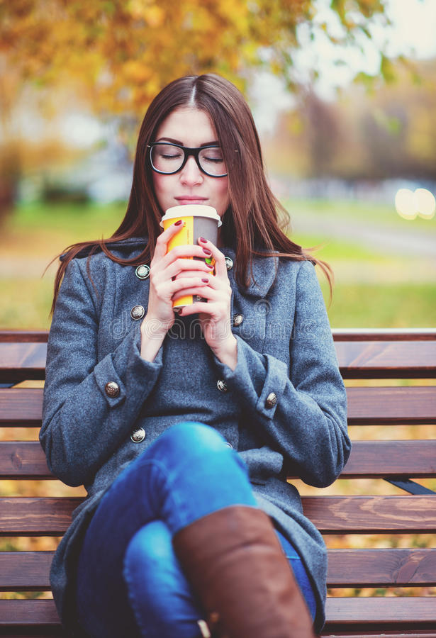 De mooie jonge vrouwenzitting op een bank het drinken koffie of de hete thee in de de lenteherfst bedekt het genieten van in park royalty-vrije stock afbeeldingen