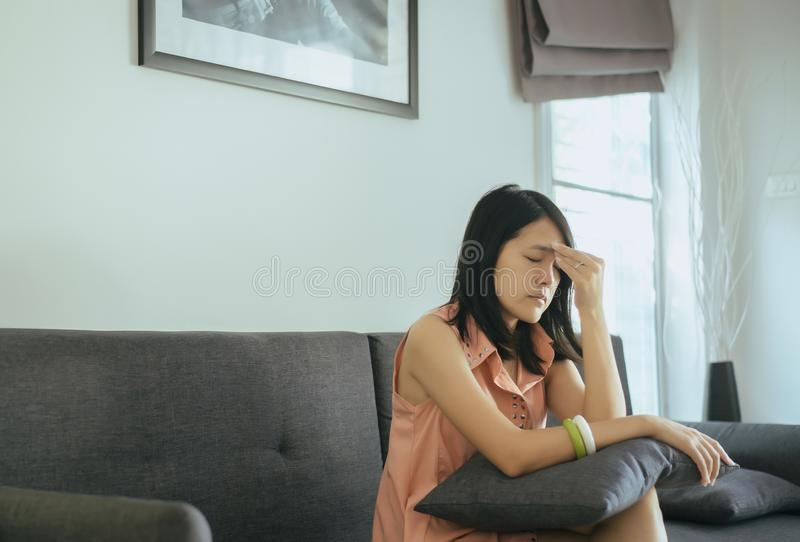 De mooie jonge vrouwenzitting op laag thuis, Wijfje die nadenkend en verward probleem voelen, houdt het hoofd met hand, Onverwach stock afbeelding