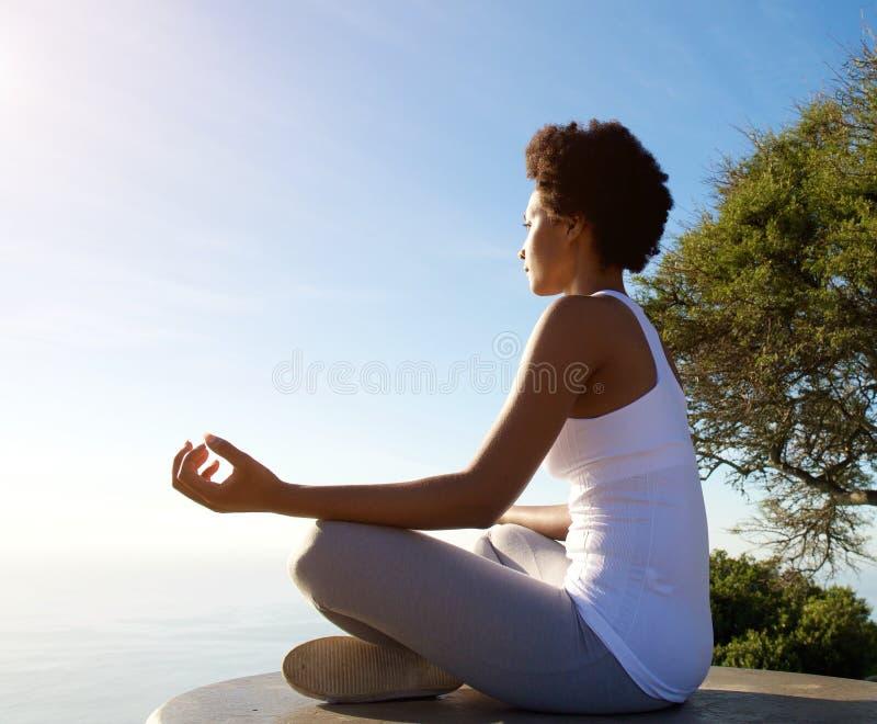 De mooie jonge vrouwenzitting in yoga stelt bij strand stock foto's