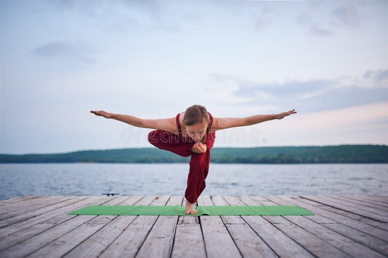 De mooie jonge yoga van vrouwenpraktijken op het houten dek dichtbij het meer royalty-vrije stock foto's