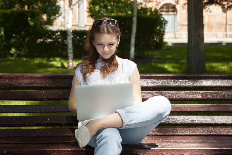 De mooie jonge zitting van het studentenmeisje op een bank met laptop en het doen van het werk aangaande freelance concept het dr stock fotografie