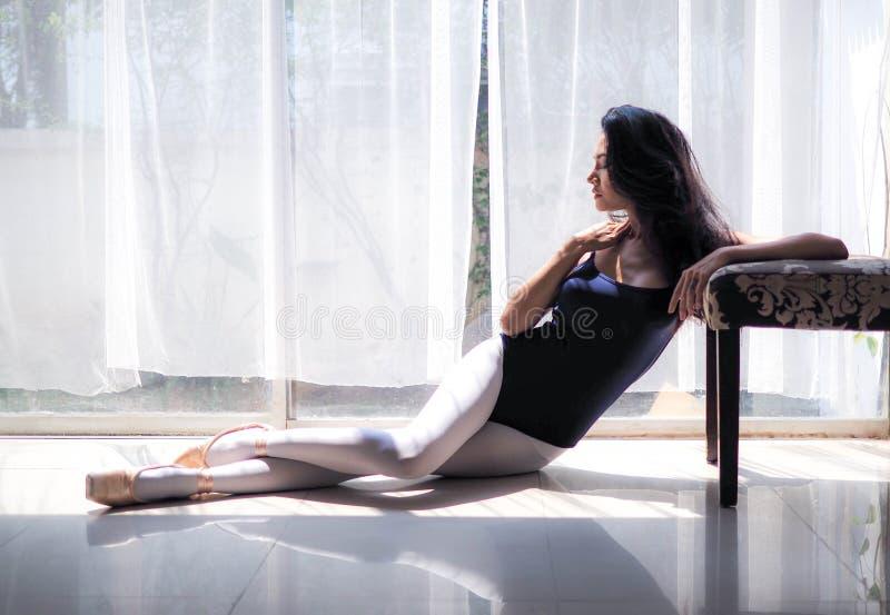 De mooie jonge zitting van de vrouwenballetdanser op de vloer stock foto