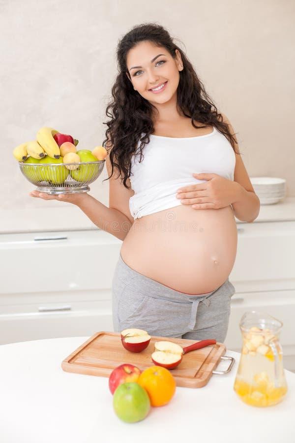 De mooie jonge zwangere vrouw verkiest gezond royalty-vrije stock fotografie