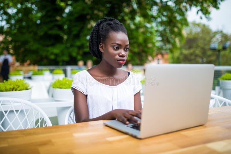 De mooie jonge zwarte vrouwelijke ondernemer zit in straatbar en werkt ver aan haar project met laptop Het charmeren Afric stock fotografie