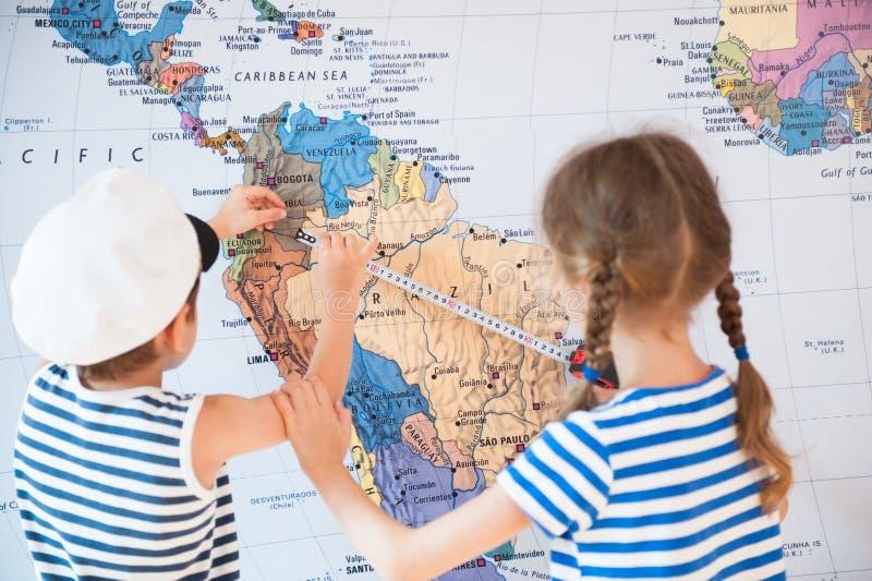 De mooie jongen en een meisje in zeemans gestreepte overhemden meten afstand op wereldkaart met het meten van band royalty-vrije stock foto's