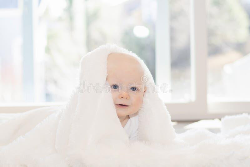 De mooie Jongen van de 6 Maandbaby kleedde zich in Wit & het Liggen op Pluizige Witte Deken Bekijkend Camera Het glimlachen & Gel stock afbeeldingen