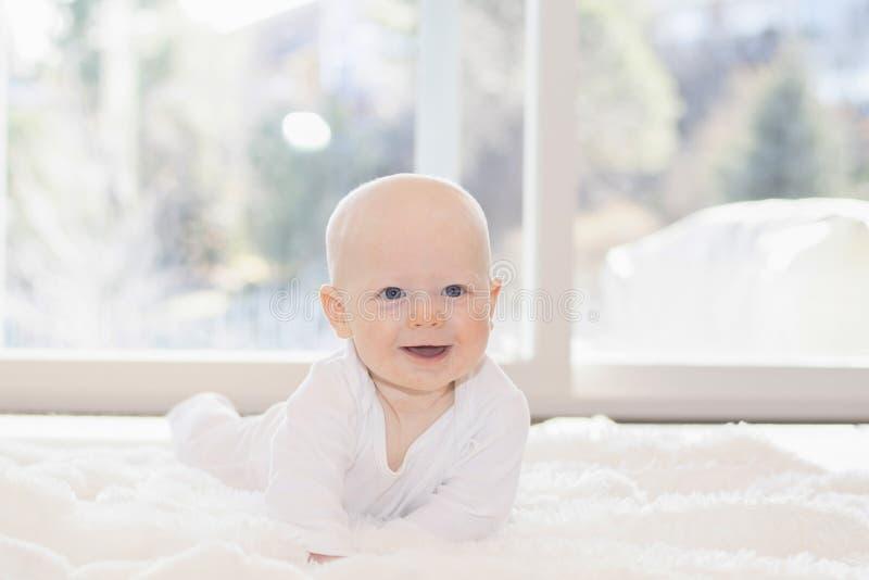 De mooie Jongen van de 6 Maandbaby kleedde zich in Wit & het Liggen op Pluizige Witte Deken Bekijkend Camera Het glimlachen & Gel royalty-vrije stock afbeelding