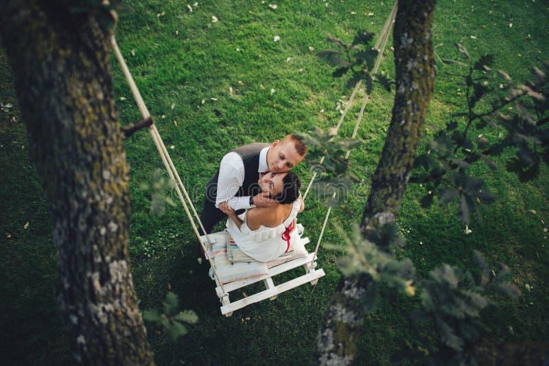 De mooie jonggehuwden kussen elkaar tedere status vóór een bri royalty-vrije stock afbeelding