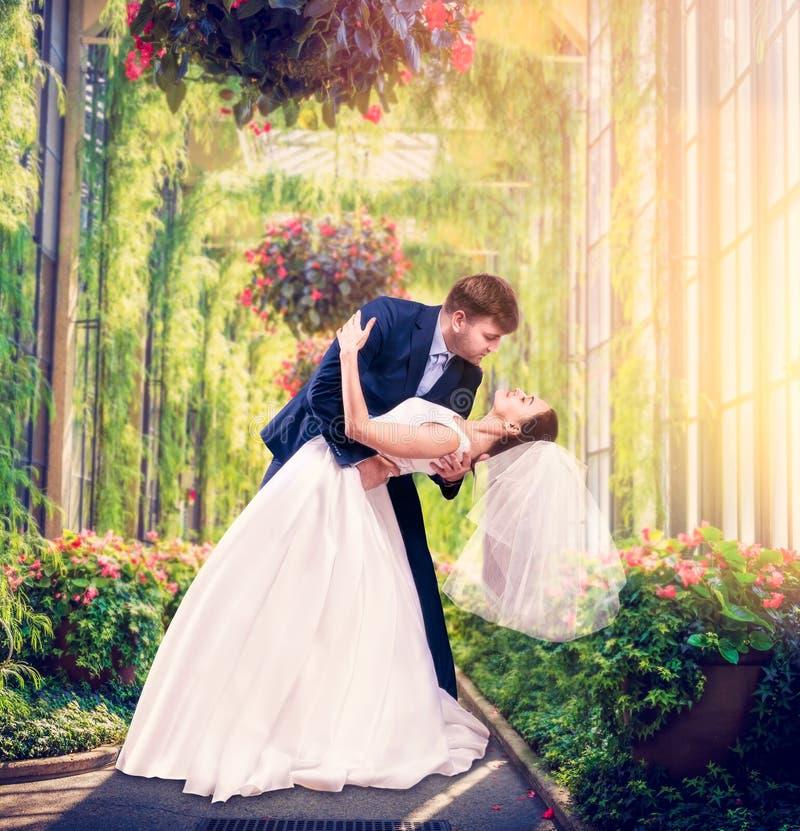 De mooie jonggehuwden omhelzen in een groene tuin royalty-vrije stock foto