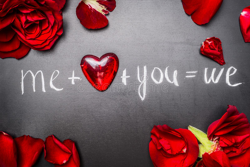 De mooie kaart van de Valentijnskaartendag met rode rozen, hart en teksten: me plus u op zwart bord stock foto