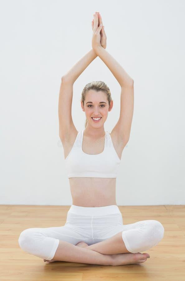 De mooie kalme vrouw die yoga doen stelt zitting op vloer in lotusbloempositie stock afbeelding
