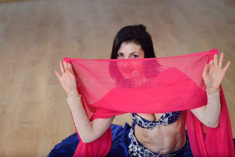 De mooie Kaukasische die vrouw in kostuum voor buikdans danst binnen bij geschiktheidsklasse in zijdesluier wordt behandeld royalty-vrije stock afbeelding