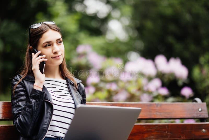 De mooie Kaukasische die vrouw zit bij de bank in een stadspark met laptop aan WiFi wordt aangesloten De ondernemer werkt aan po stock afbeeldingen