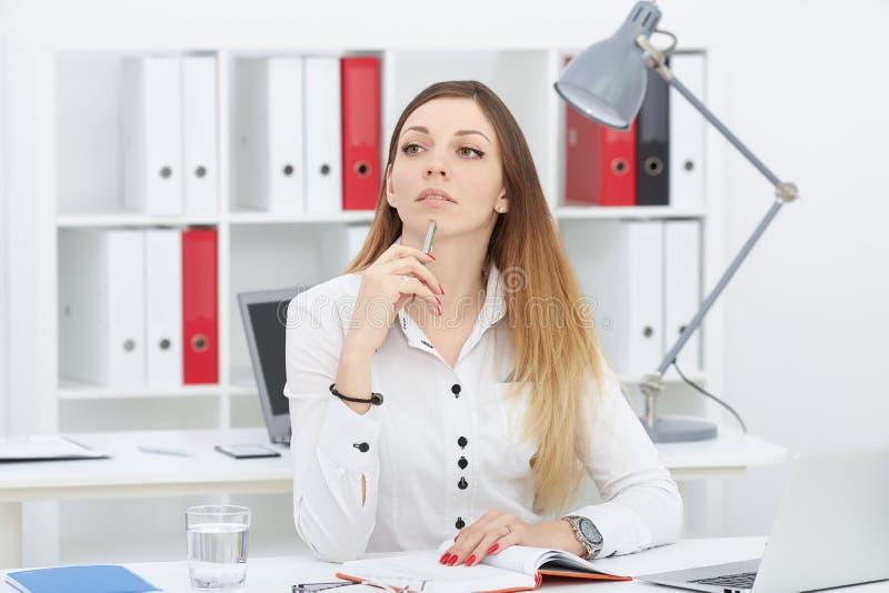 De mooie Kaukasische jonge bedrijfsvrouw onderzoekt de afstand, zittend op het haar werk stock foto's