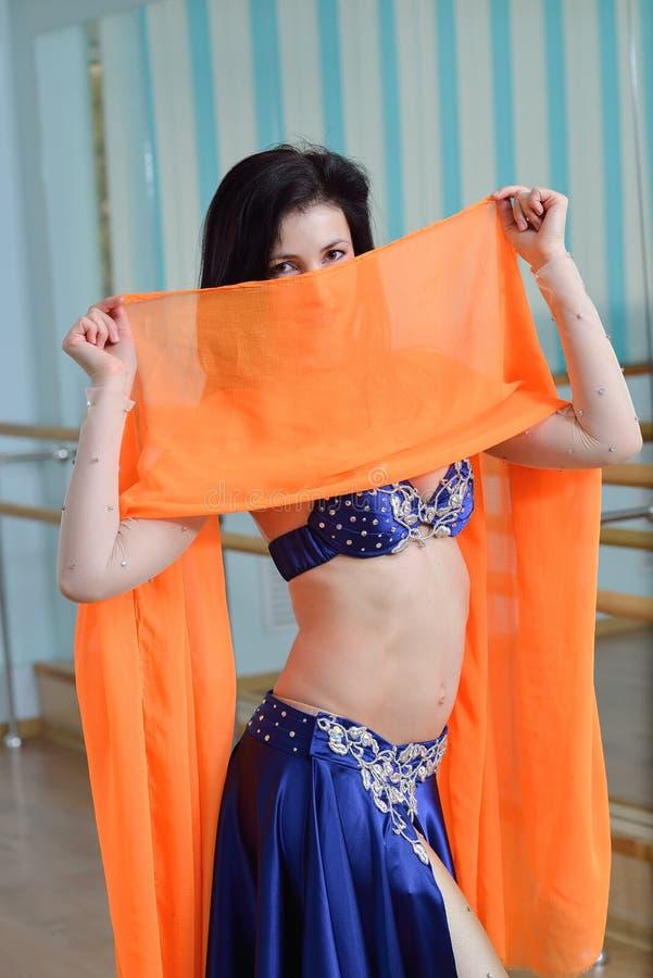 De mooie Kaukasische vrouw in kostuum voor buikdans danst binnen bij geschiktheidsklasse stock afbeelding