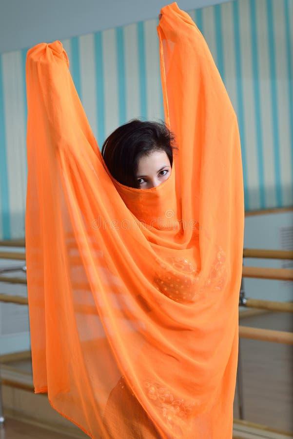 De mooie Kaukasische vrouw in kostuum voor buikdans danst binnen bij geschiktheidsklasse stock afbeeldingen