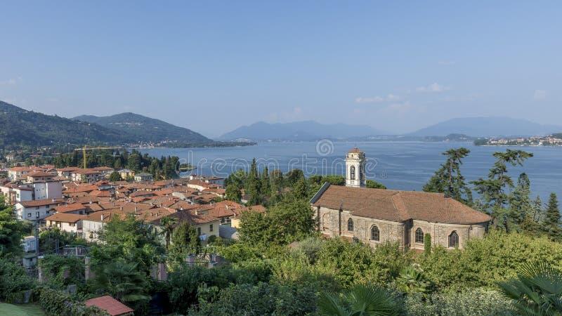 De mooie Kerk van Santa Margherita in Meina, die het meer van Maggiore, Novara, Italië over het hoofd ziet stock foto's