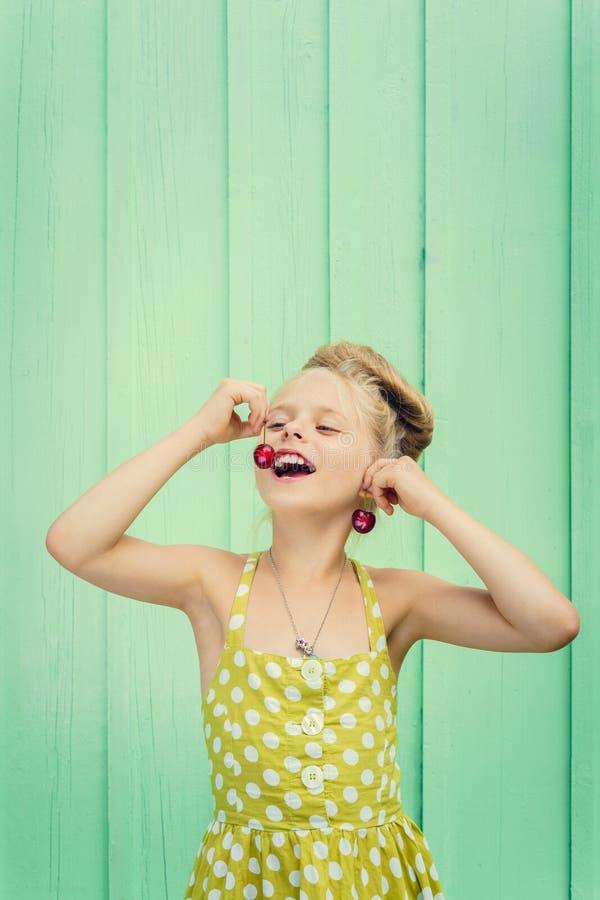 De mooie kersen van de meisjesholding als oorringen - stijl Rockabilly stock fotografie