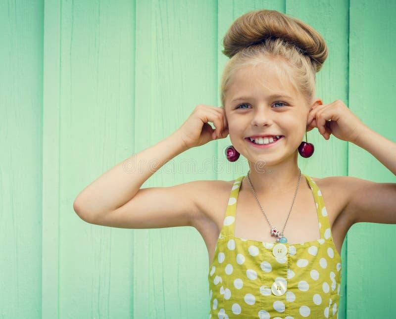 De mooie kersen van de meisjesholding als oorringen - stijl Rockabilly royalty-vrije stock foto