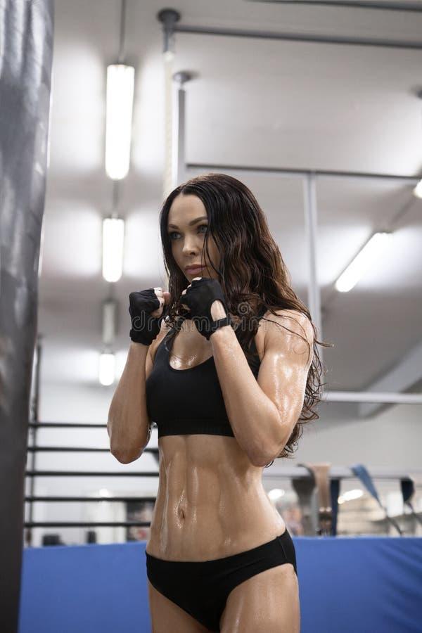 De mooie Kickboxing-vrouw zak van het opleidingsponsen in geschiktheidsstudio royalty-vrije stock foto