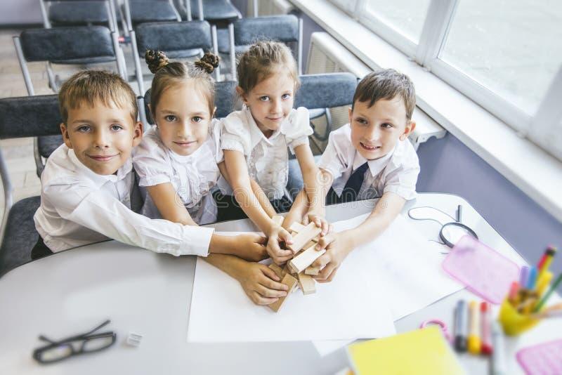De mooie kinderen bedragen studenten samen in een klaslokaal s stock afbeeldingen