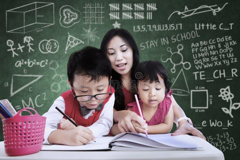 De mooie kinderen van de leraarshulp om in klasse te schrijven stock fotografie