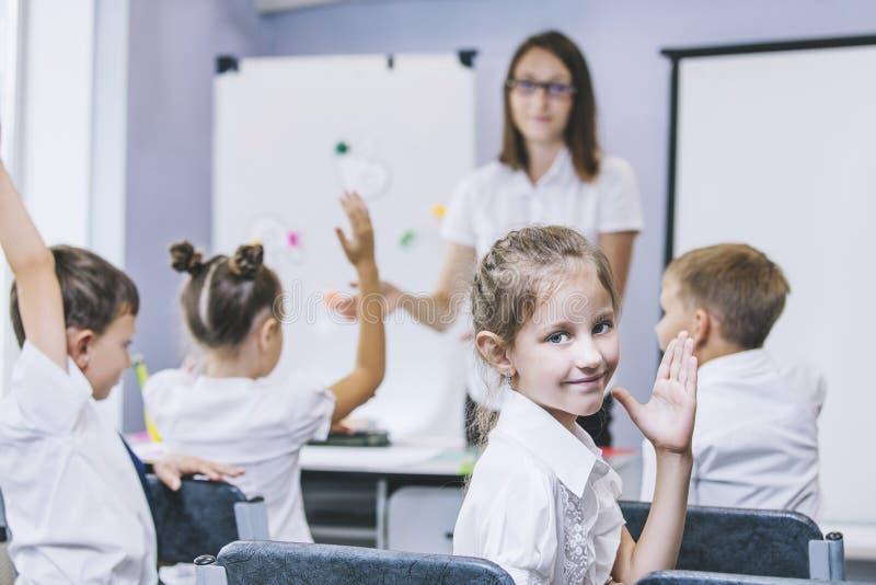De mooie kinderen zijn studenten samen in een klaslokaal in schoo stock afbeeldingen