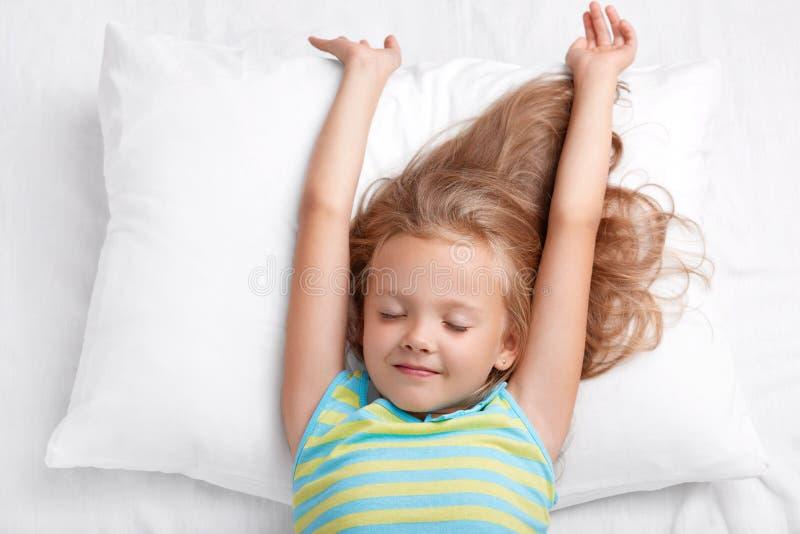 De mooie kleine aanbiddelijke jong geitjerek in bed, gekleed in toevallige pyjamass, ligt op wit comfortabel hoofdkussen, houdt o royalty-vrije stock afbeelding