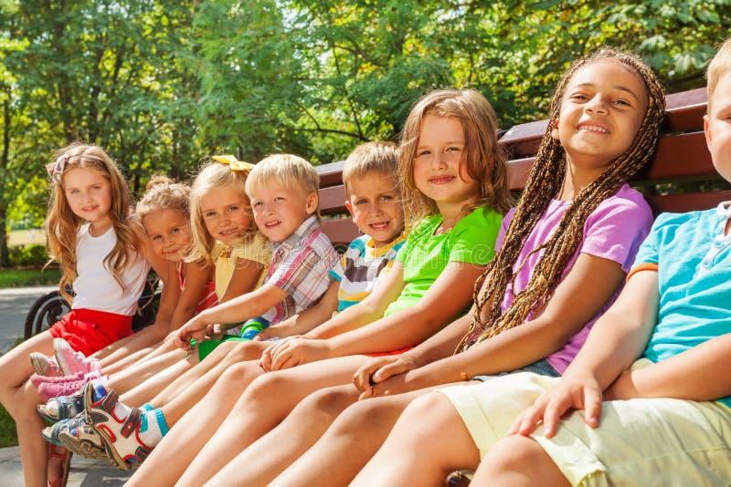 De mooie kleine kinderen zitten op bank in park stock fotografie