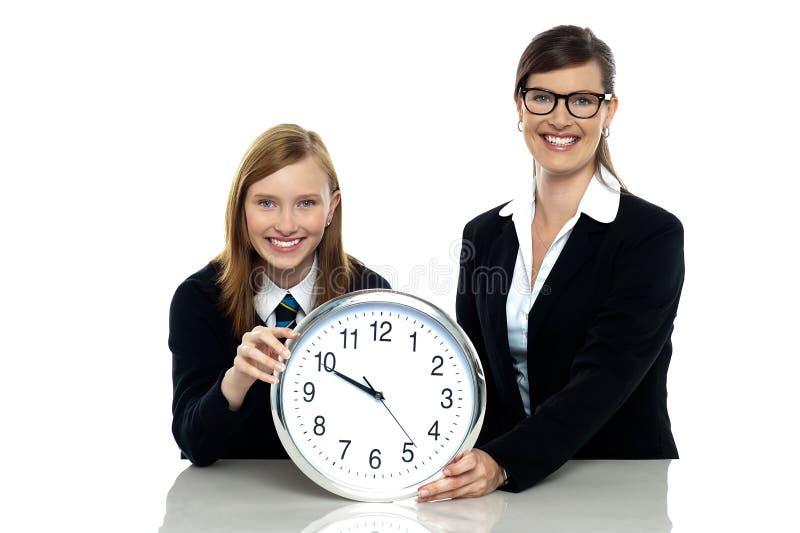 De mooie klok van de studentenholding met haar leraar stock fotografie
