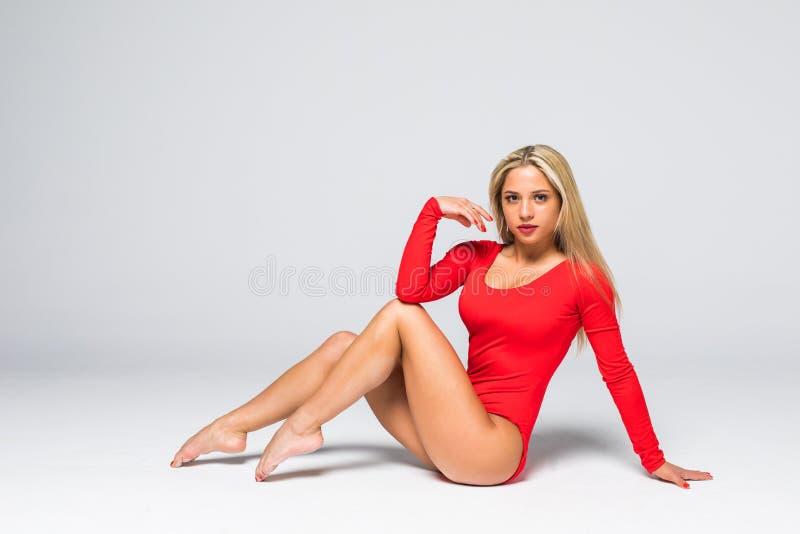 De mooie koele jongelui past turnervrouw in het rode element van de de uitvoerende kunstgymnastiek van de sportkledingskleding op stock afbeeldingen